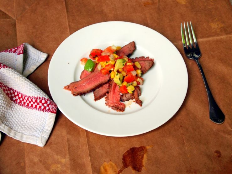 thinly sliced flank steak piled on a white plate with avocado corn salsa on top.