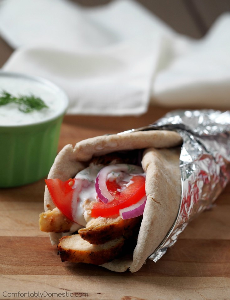 grilled chicken gyro rolled in a pita with tomato, onion, and tzatziki sauce on a cutting board.