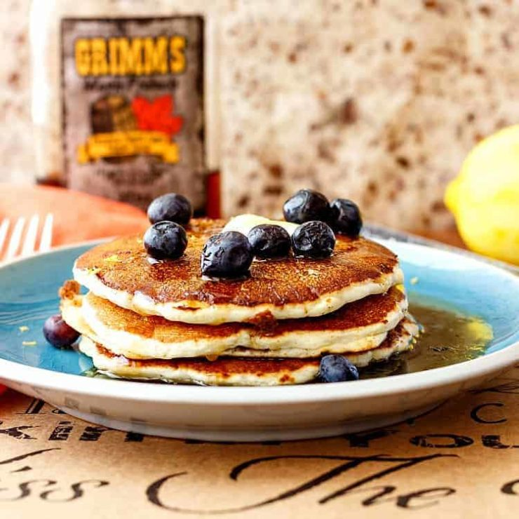 stack of pancakes on a green plate with blueberries on top.