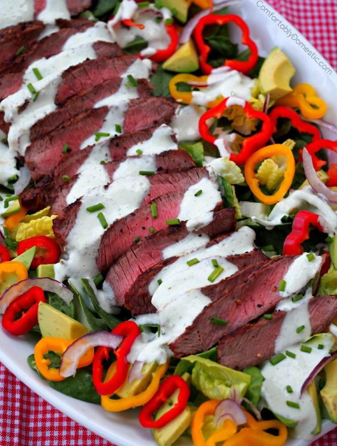 sliced grilled steak on a bed of mixed greens with colorful sweet peppers and drizzled with yogurt dressing.