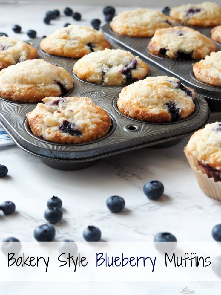 bakery style blueberry muffins in a vintage muffin tin set on white a marble background.