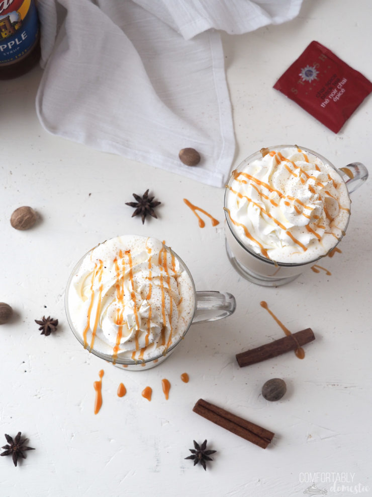 Overhead photo of two mugs of caramel apple chai latte with whipped cream and caramel on a white background.