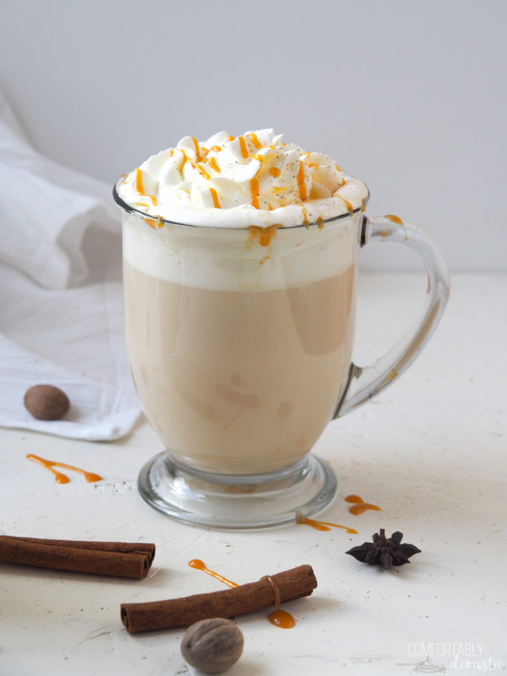 Caramel Apple Chai Latte in a glass mug with whipped cream, freshly grated nutmeg, and caramel sauce.