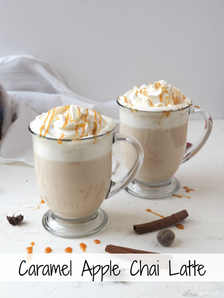 Two glass mugs of caramel apple chai latte with whipped cream, grated nutmeg, and caramel on top.