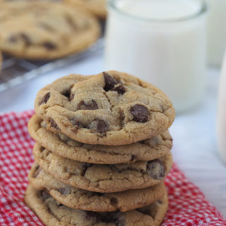 Stack of Mrs. Field's Chocolate Chip Cookies resting on a red gingham napkin.