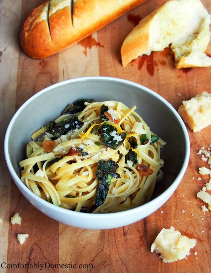 white-bowl-of-lemon-garlic-linguine-with-fresh-kale on a cutting board with a baguette and crumbled parmesan