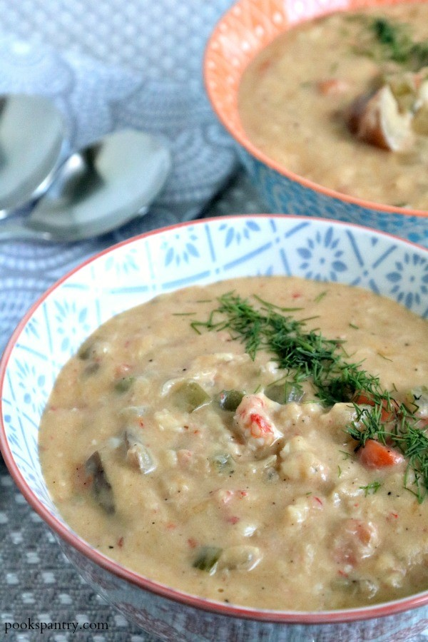 Bowl of Langostino lobster chowder in a gray background.