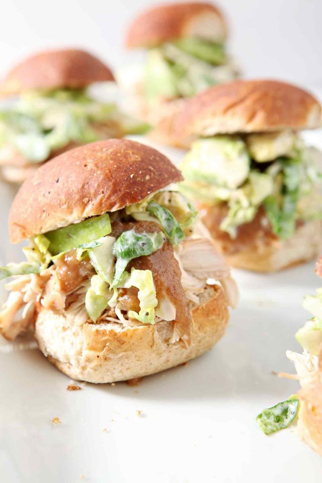 Several apple pulled chicken sliders on buns on a white platter.