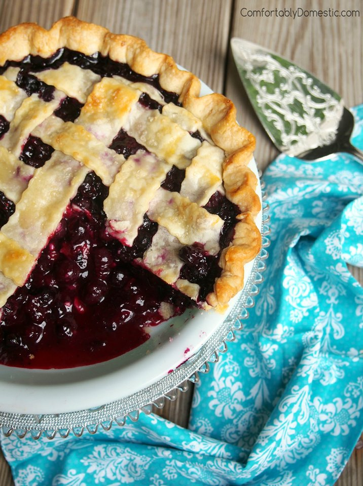 Sliced lattice topped photo of the Best Blueberry Pie in a white pie plate.