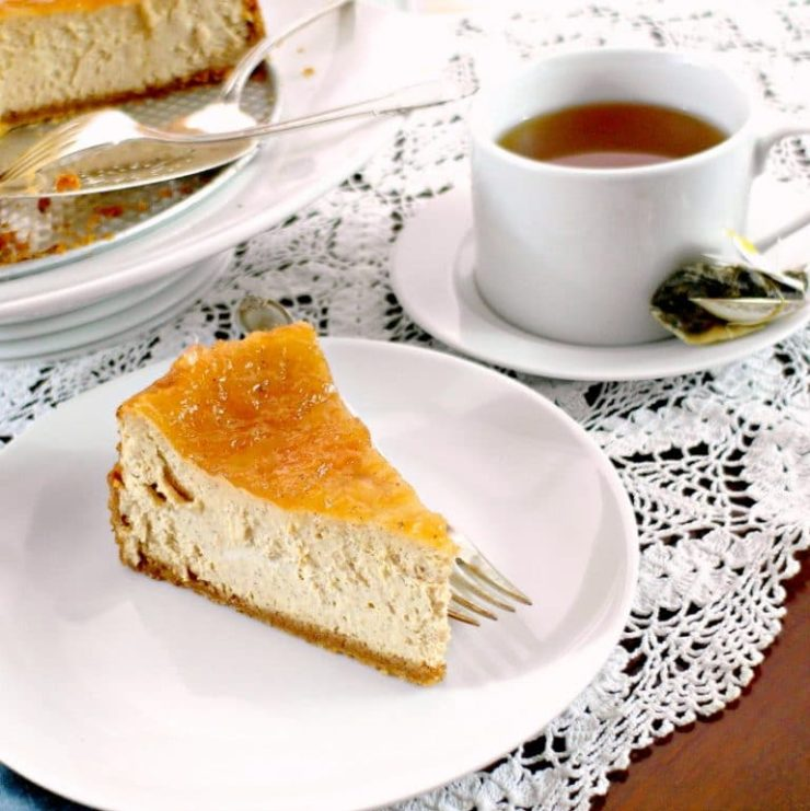 slice of cinnamon cheesecake on a white plate with a cup of tea.