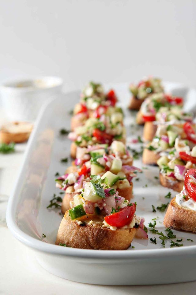 Rows of Greek bruschetta on a white platter.