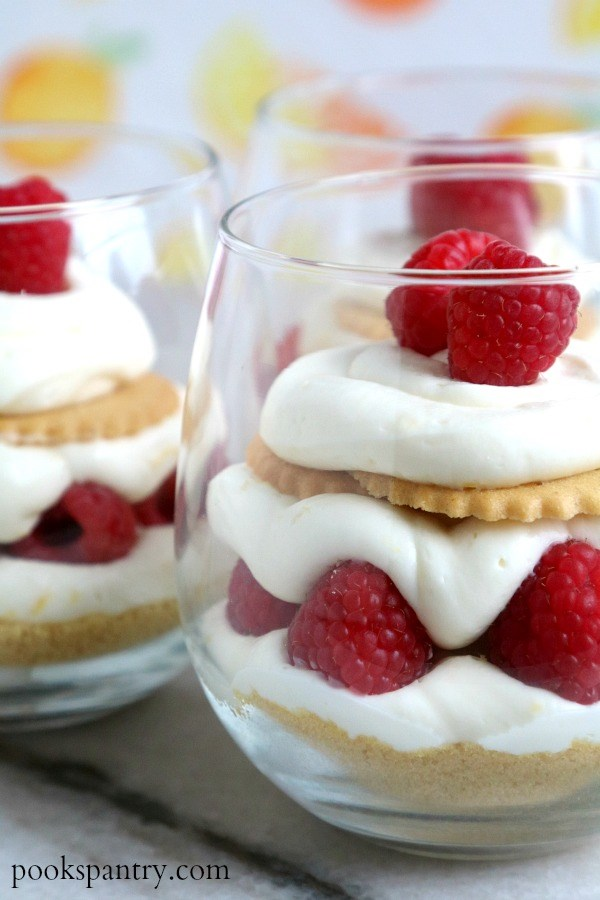 Two clear glasses of no bake lemon cheesecake parfaits on a white background.
