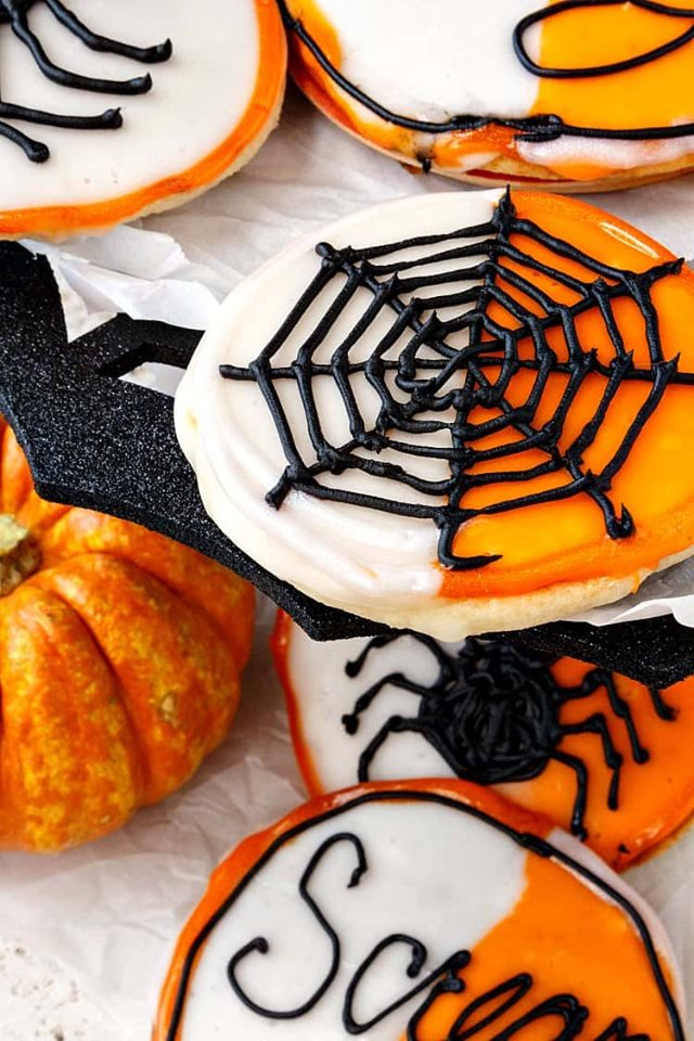 Halloween-black-and-white-cookies with spiders and webs piped on top.