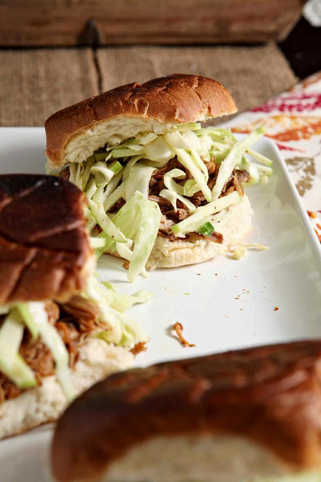 several apple-cider-pulled-pork-sandwiches with cabbage slaw on a square white plate.