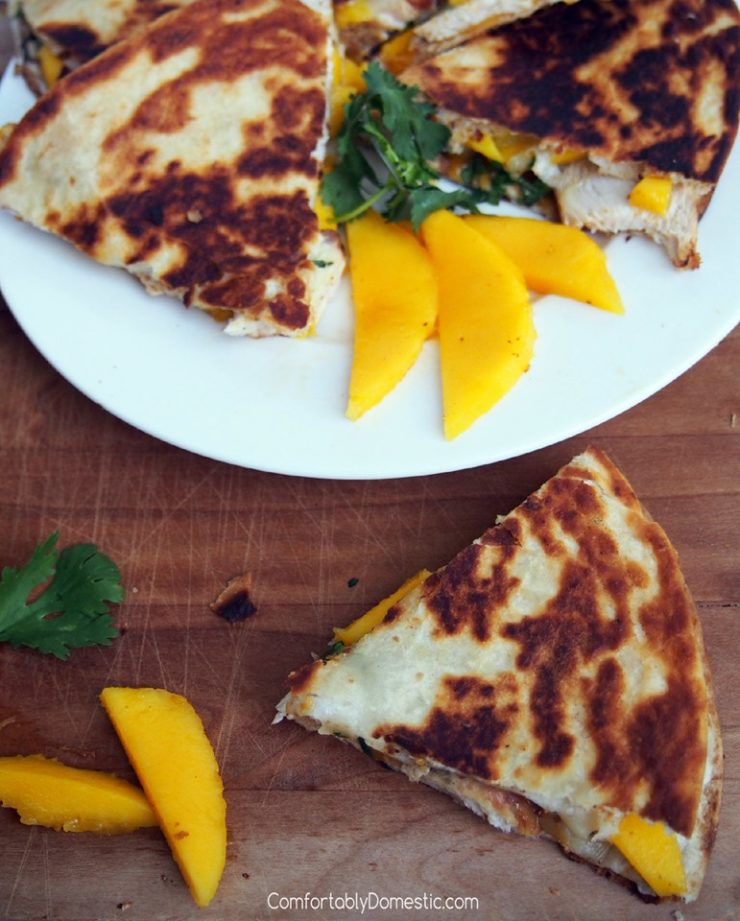 Wedges of chicken-mango-quesadillas-with-brie on a white plate and wooden cutting board.