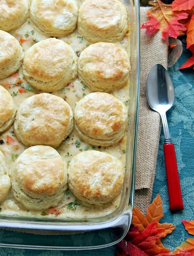 Casserole dish with golden biscuits with turkey pot pie filling underneath.