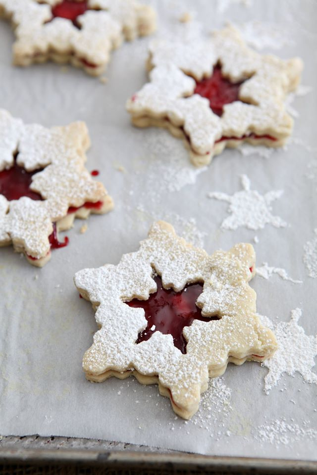 A trio of raspberry linzer snowflake cookies on parchment paper.