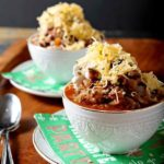 Two white bowls heaping with shiner bock flavored chili and cheese.