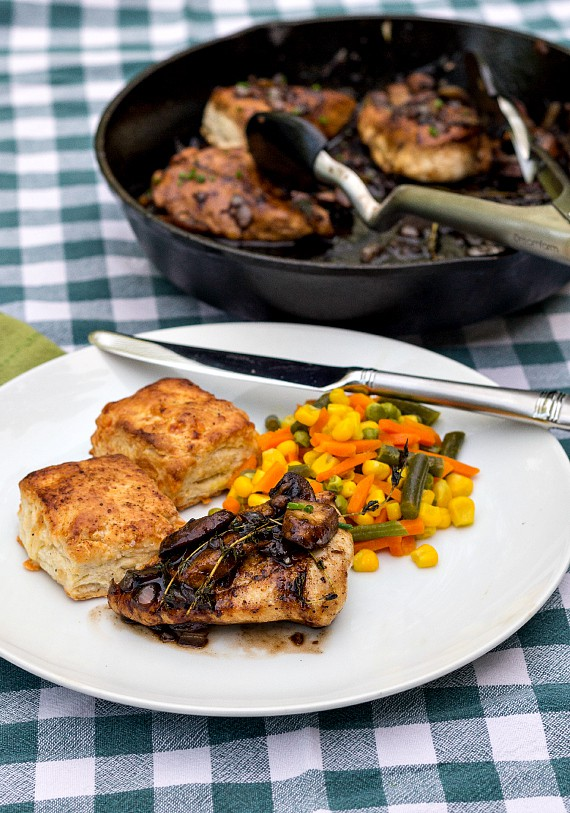Chicken-with-mushrooms and thyme served with biscuits and mixed vegetables on a white plate on a blue gingham background.