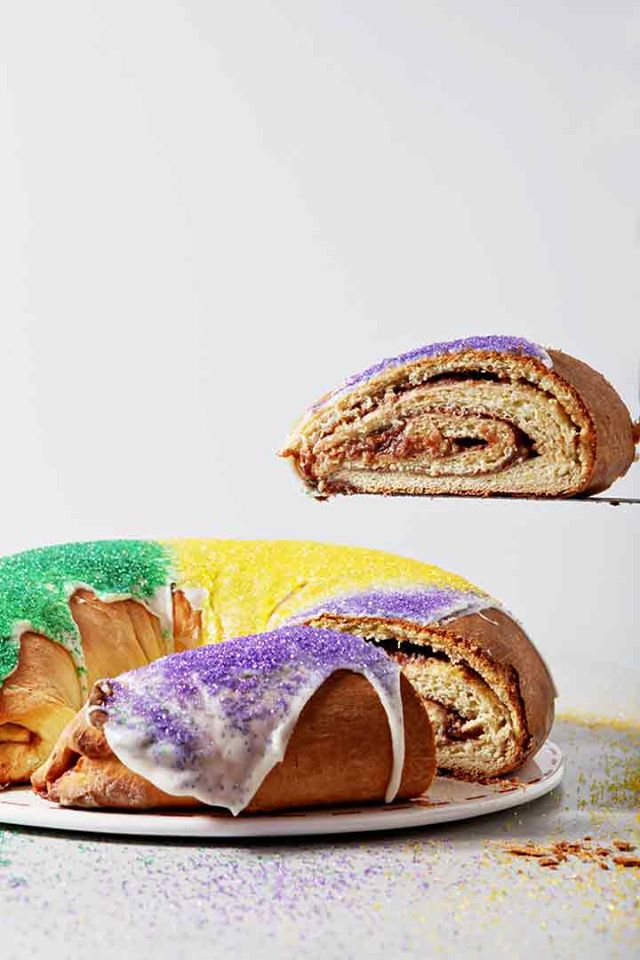 Golden ring of cream cheese and raspberry filled king cake with red, yellow, and purple sugar on top.
