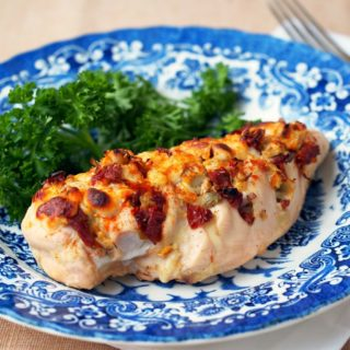 Hasselback-Stuffed-Chicken filled with cheese, artichoke hearts, and sundried tomatoes on a blue and white plate.