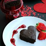 A stunning dark chocolate cake in the shape of a heart with red wine ganache swirled on a white plate.