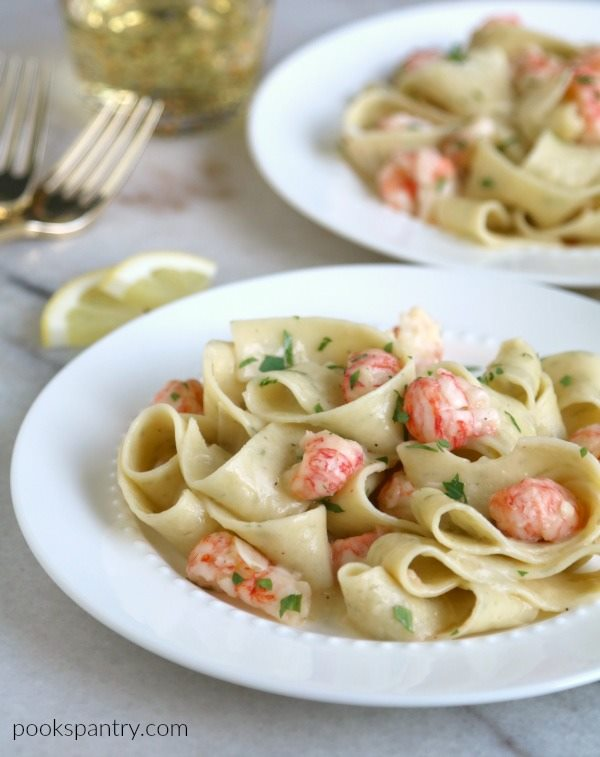 Gorgeous bowl of fresh pasta with tender langostinos on top in a wide brimmed white bowl.