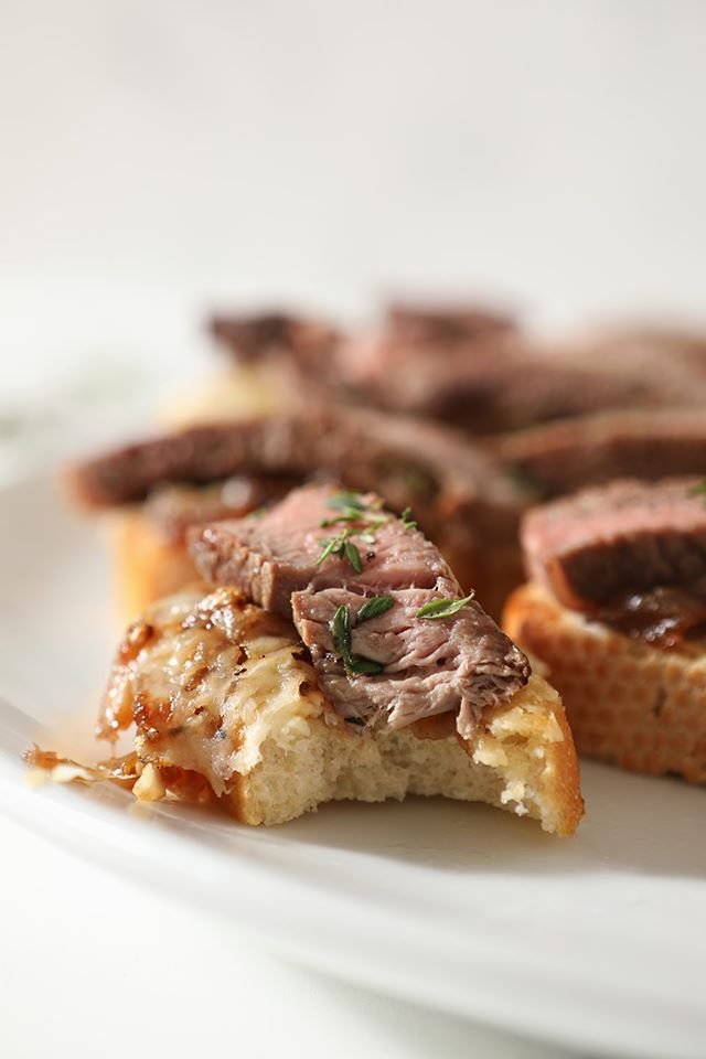 Crispy bites of toast with steak and french onion marmalade on a white plate.