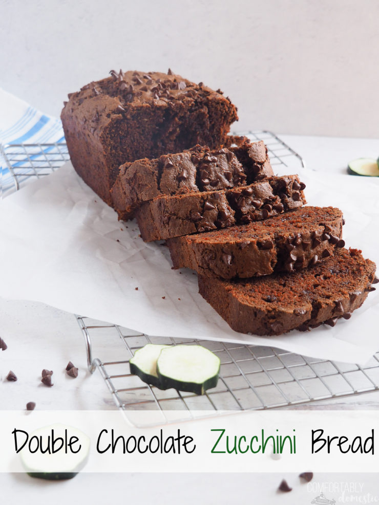A sliced loaf of double chocolate zucchini bread  resting on parchment paper while cooling on a rack..