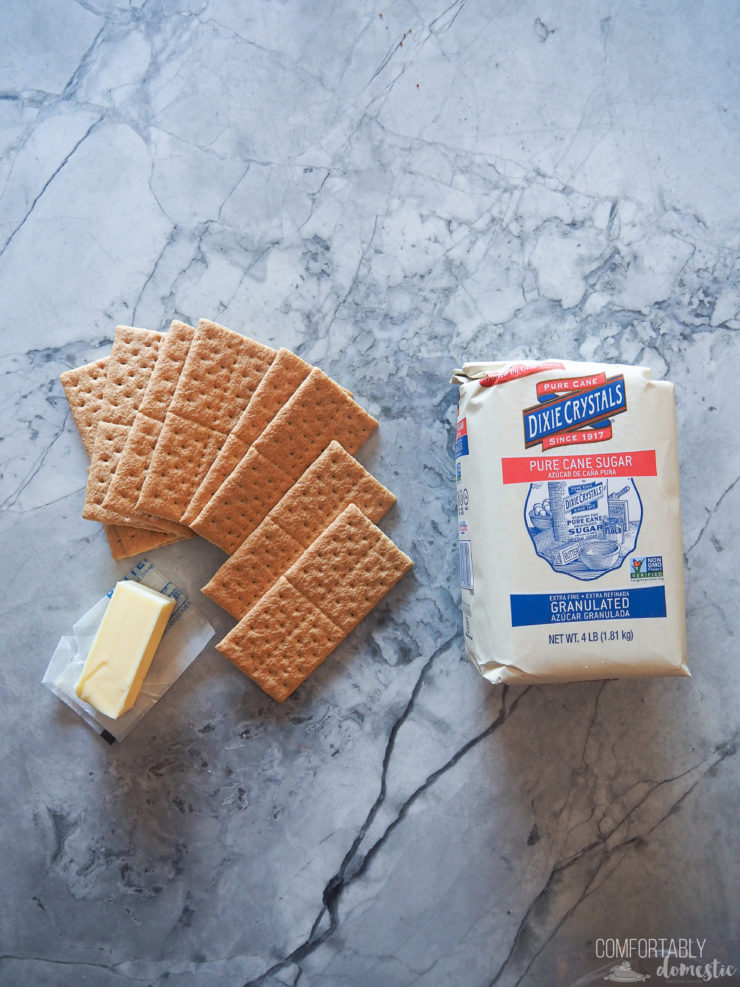 Graham crackers, butter and sugar set on white marble to make perfect crust.